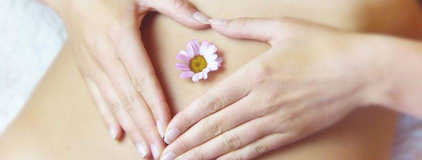 Vientre de mujer con sus manos rodeando una flor en su ombligo