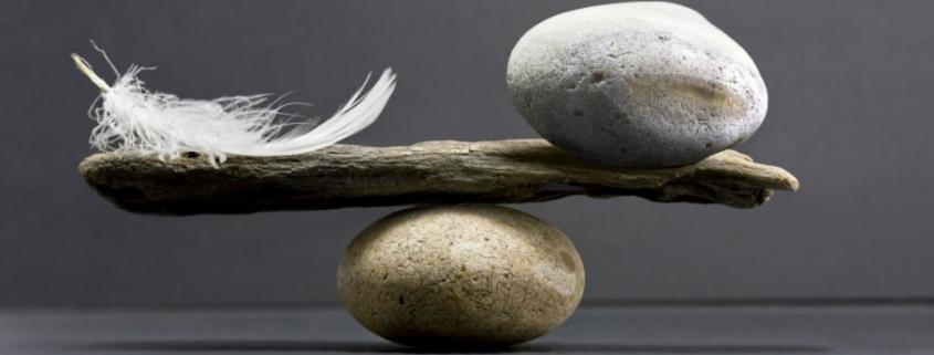 Balanza equilibrada con piedra y pluma