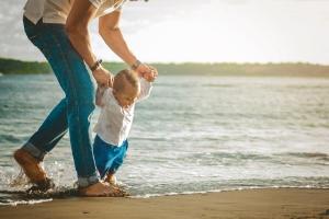 Bebé aprendiendo a caminar en la playa